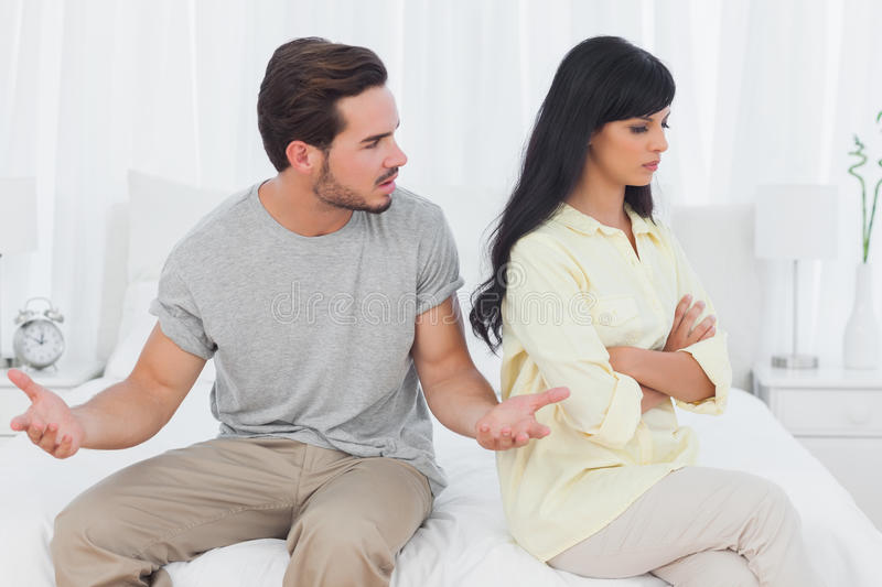 Woman sulking while her boyfriend is explaining himself stock photos