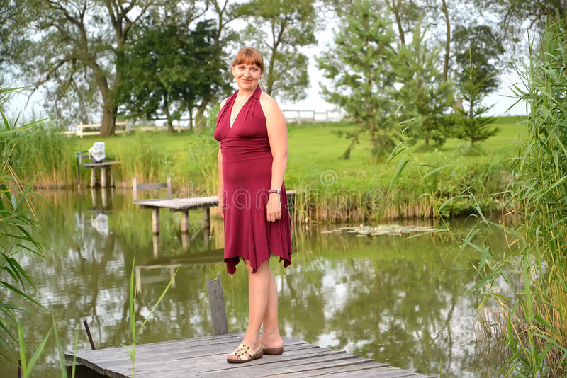 The woman in a summer claret dress stands on a planked footway near a pond.  royalty free stock photo