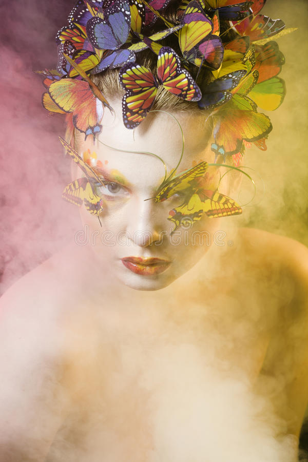 Woman with summer creative make up like fairy. Butterfly closeup bright colored background black stock photography