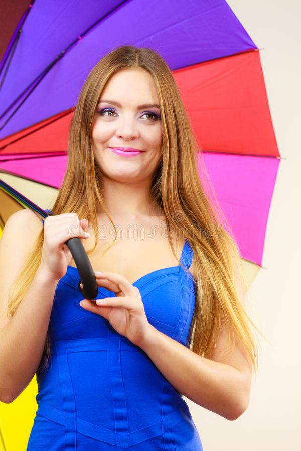 Woman in summer dress holds colorful umbrella stock photo