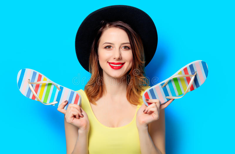 Woman with summer flip-flops. Portrait of young smiling red-haired white european woman in hat with summer flip-flops on blue background stock photo