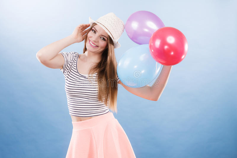 Woman summer joyful girl with colorful balloons. Woman joyful girl playing with colorful balloons. Summer, celebration and lifestyle concept. Studio shot blue stock photography