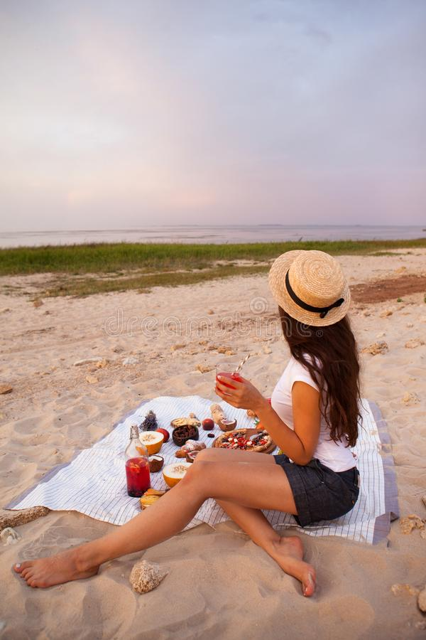 Woman in summer Picnic on the beach at sunset in the white plaid stock photo