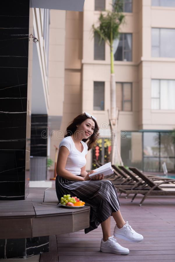 Woman in summer reading a book by the swimming pool. Vacation and relaxation, summer travel concept royalty free stock photos