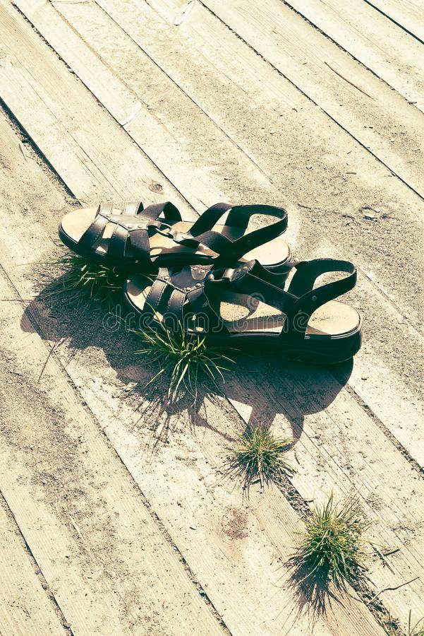 Woman summer sandals in warm sunshine on wooden planks with sand and grass, with free empty space for copy. Concept of relaxing vacation, summertime travel stock images