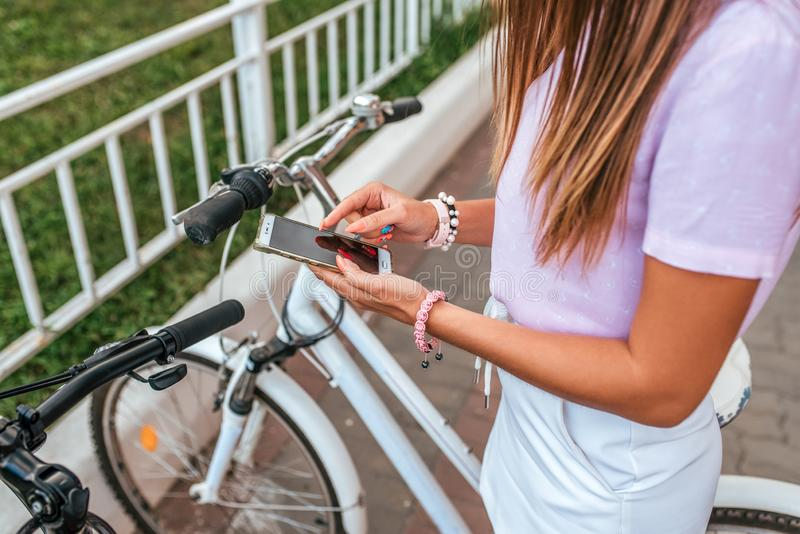 A woman summer stands bicycle, activates application buying rental bicycle in parking lot, in hands of phone. Online royalty free stock image