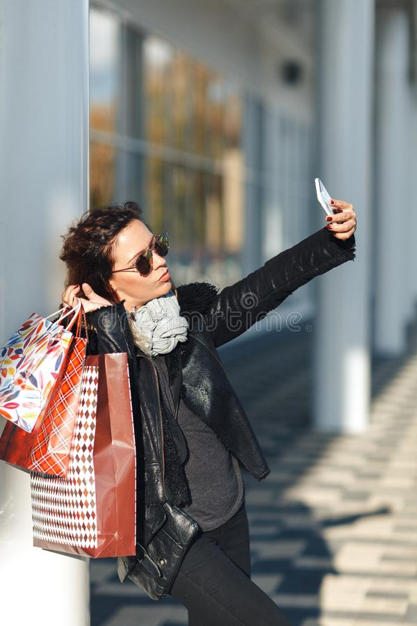 Woman in sun glasses a black leather jacket, black jeans Holding a Bunch of Shopping Bags Doing Selfie in front of mirrored window. S on the Street stock photos