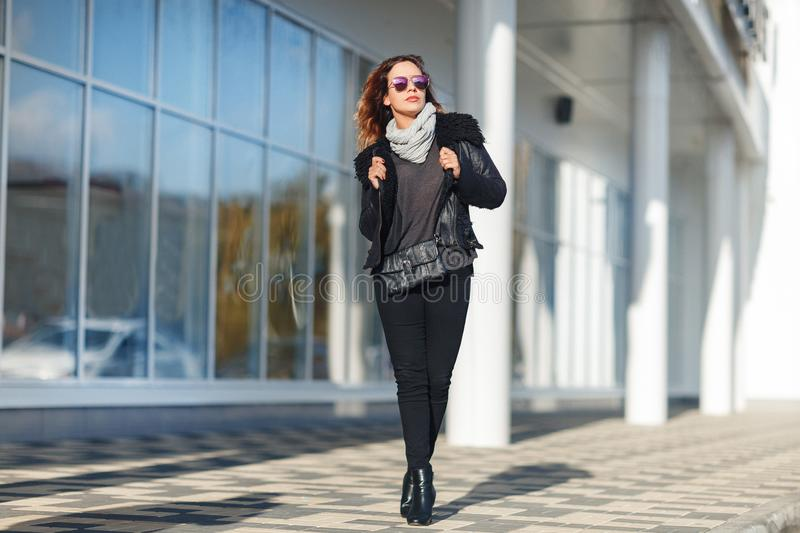 Woman in sun glasses a black leather jacket, black jeans posing in front of mirrored windows. Female fashion concept. Outdoor. stock images