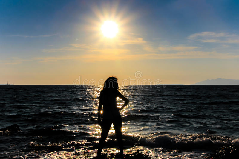 Woman and sun. Shadowy figure of woman on background of sea and sun stock photography