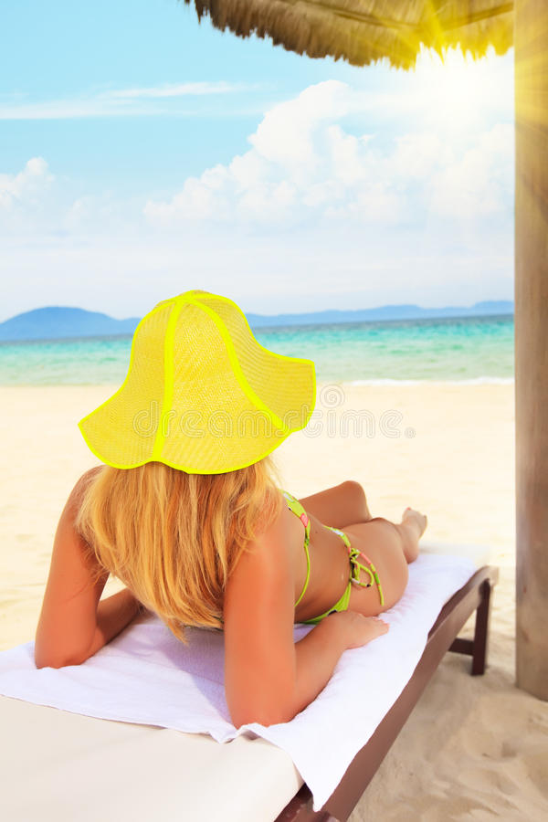 Woman sunbathing. Young woman sunbathing on the chair near the ocean royalty free stock image