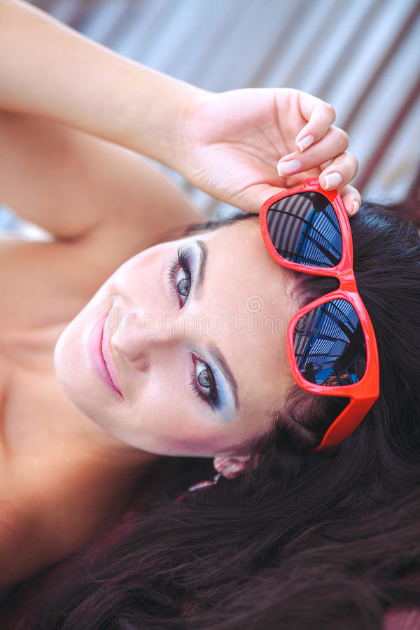 Woman sunbathing in bikini at tropical travel resort. Beautiful young woman lying on sun lounger near pool. stock images