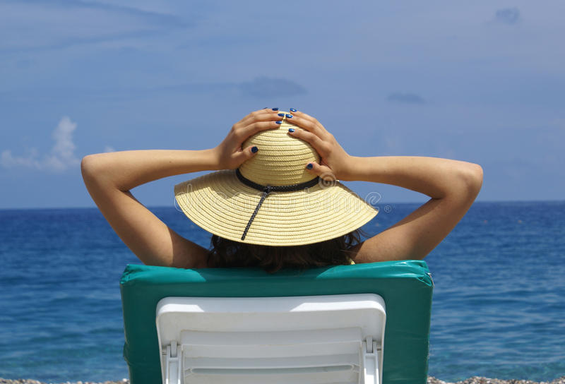 Woman sunbathing in a plastic chair on a beautiful royalty free stock photography