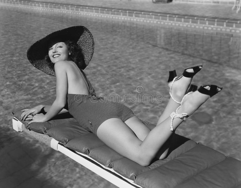 Woman sunbathing at pool stock images