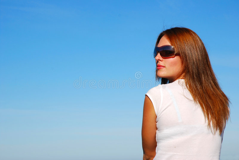 Woman with sunglasses. A beautiful young woman model with long red hair, wearing sunglasses and staring in front of blue sky background in summer outdoors stock photos