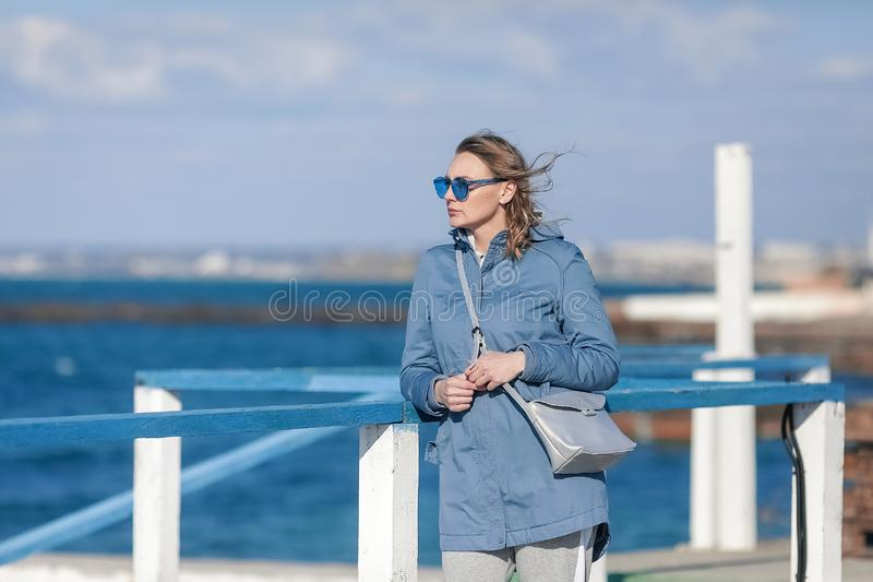 Woman in sunglasses against the background of a wooden wall royalty free stock images