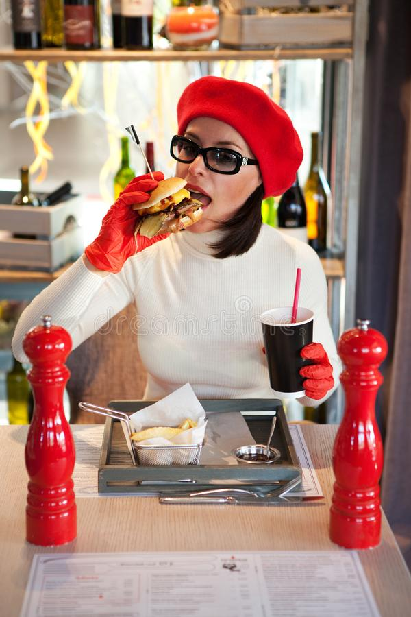 Woman in sunglasses is biting burger in restaurant royalty free stock images