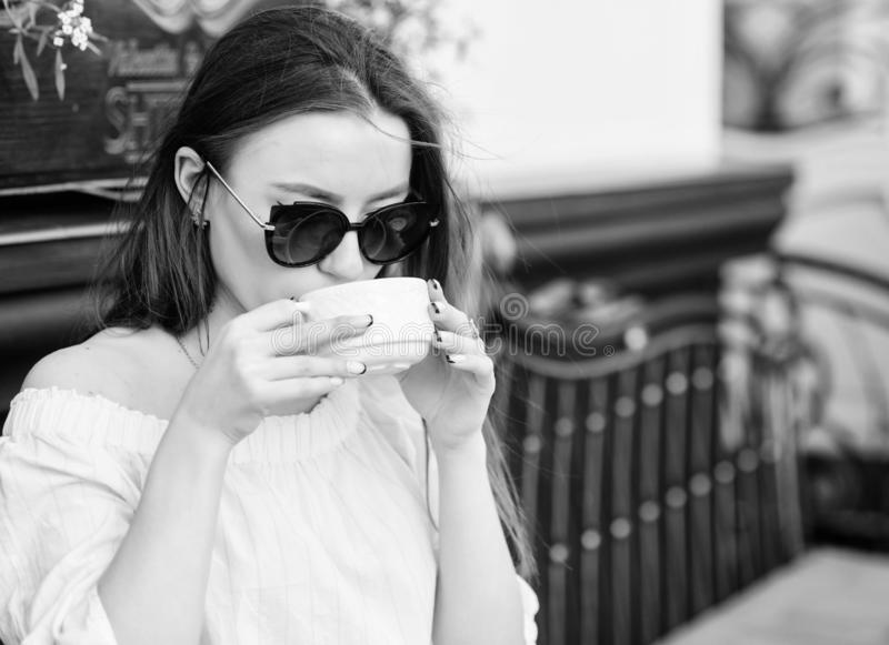 Woman in sunglasses drink coffee outdoors. Girl relax in cafe cappuccino cup. Caffeine dose. Coffee for energetic stock image