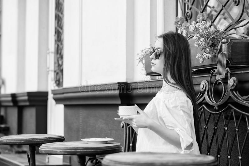 Woman in sunglasses drink coffee outdoors. Girl relax in cafe cappuccino cup. Caffeine dose. Coffee for energetic royalty free stock photos