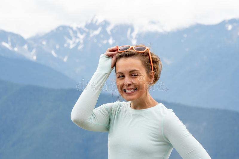 Woman with sunglasses perched on head squints and poses at Hurricane Ridge in Washington States Olympic National Park.  royalty free stock images