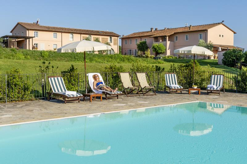Woman with sunglasses relaxes lying on a lounger by the pool of a resort in the countryside of Pisa, Tuscany, Italy royalty free stock photography
