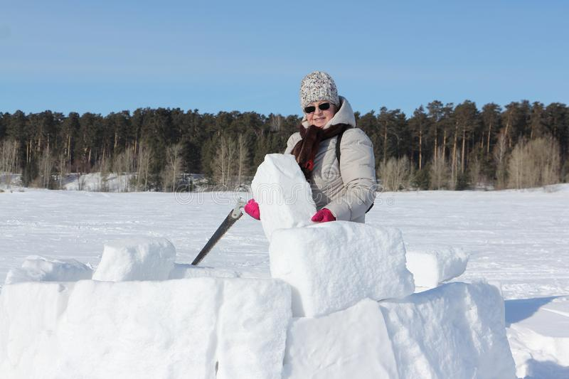 Woman in sunglasses with a saw in a  hand building an igloo, Novosibirsk, Russia stock photo