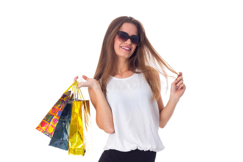 Woman in sunglasses with shopping bags. Young happy woman in white blouse and black skirt with dark sunglasses holding shopping bags on white background in royalty free stock photos