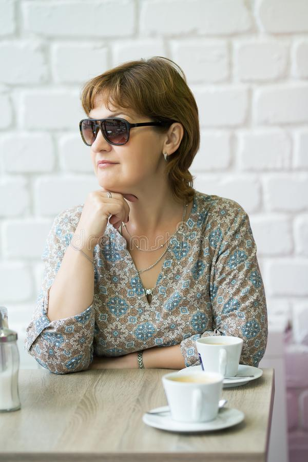 Woman in sunglasses sits at a table. In a cafe royalty free stock image