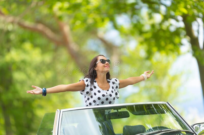 Woman in sunglasses sits on top of the convertible, arms wide open, soaking up the sun and fresh air stock photo
