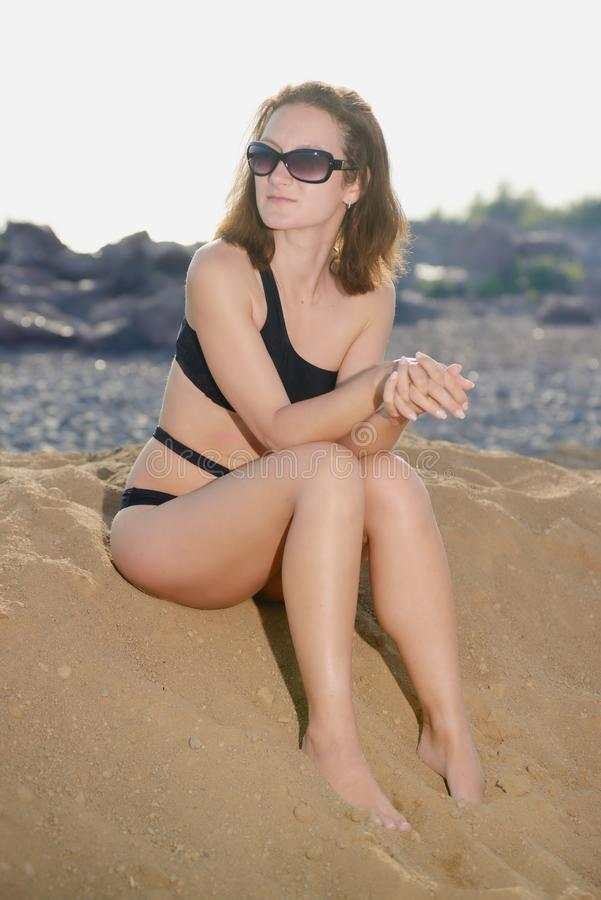 Woman in sunglasses sitting on beach royalty free stock photos