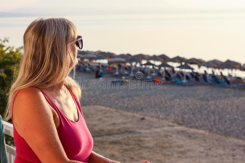Woman with Sunglasses Standing on the Balcony Early in the Morning During the Sunrise and Looking at the Sea stock photo