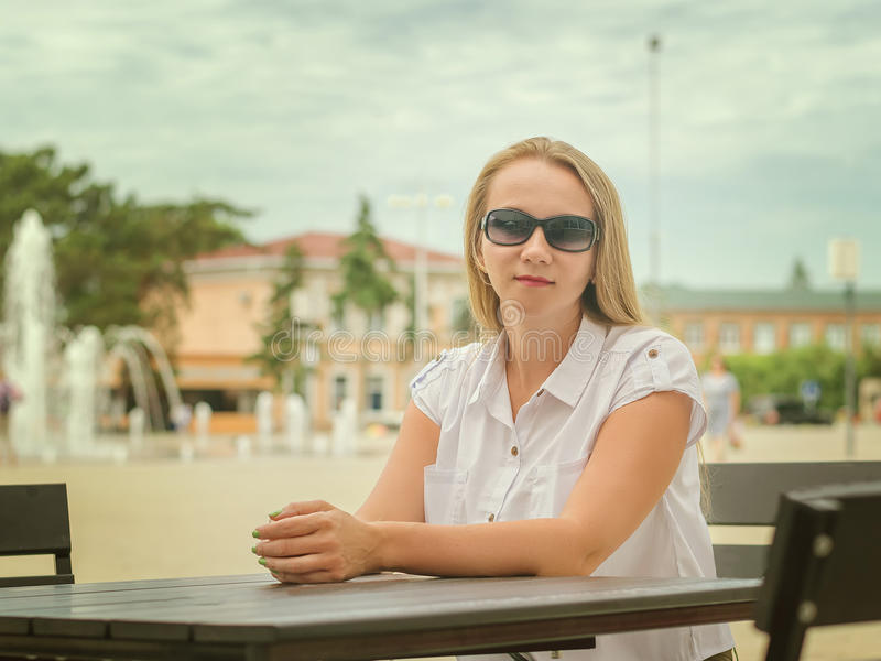 Woman in sunglasses at a table in summer cafe. stock photo