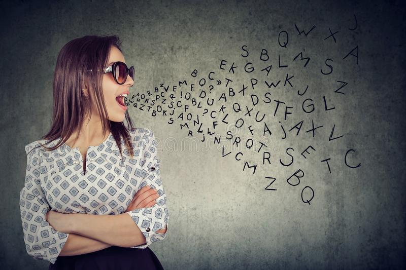 Woman in sunglasses talking with alphabet letters coming out of her mouth. stock images
