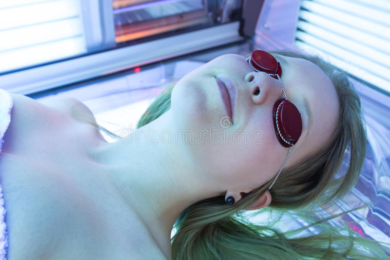 Woman with sunglasses on tanning bed in solarium royalty free stock image