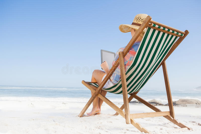 Woman in sunhat sitting on beach in deck chair using tablet pc. On a sunny day stock photography