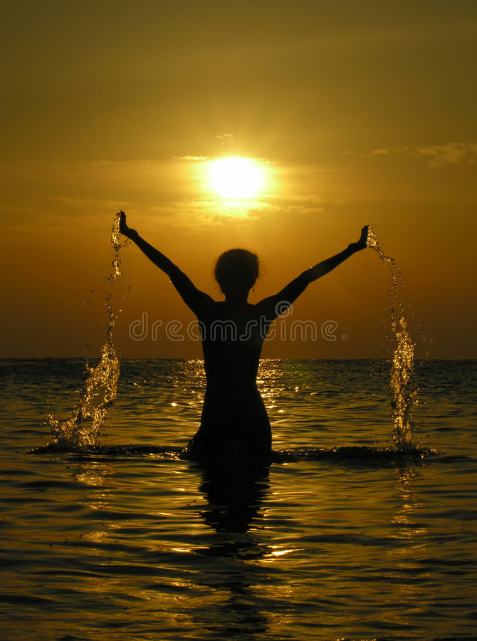 Woman at sunrise with drops of water. Beach stock image