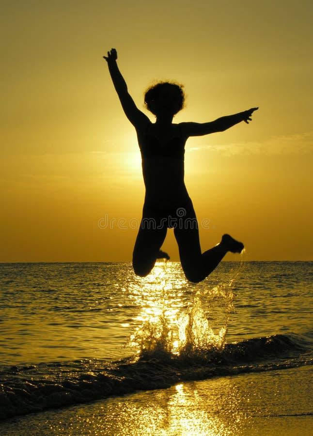 Woman at sunrise jump royalty free stock photo