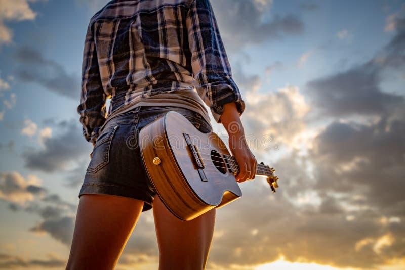 Woman at sunset holding a ukulele stock photo