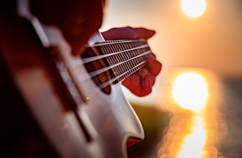 Woman at sunset playing the ukulele royalty free stock image