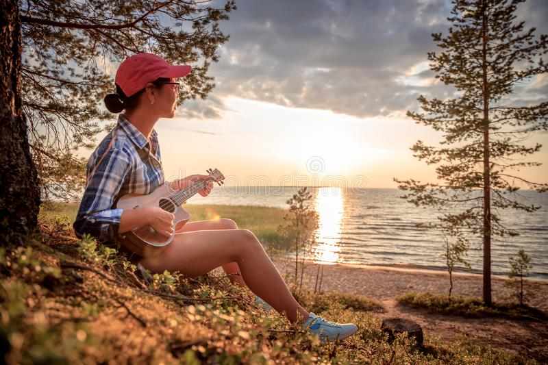 Woman at sunset playing the ukulele royalty free stock image