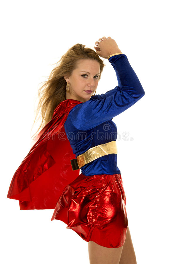 Woman super hero red cape blowing hands up. A super hero woman with her cape flying and flexing her arms royalty free stock photo
