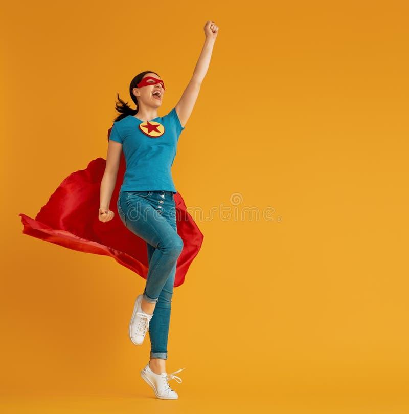 Woman in superhero costume. Joyful beautiful young woman in superhero costume posing on yellow background royalty free stock images