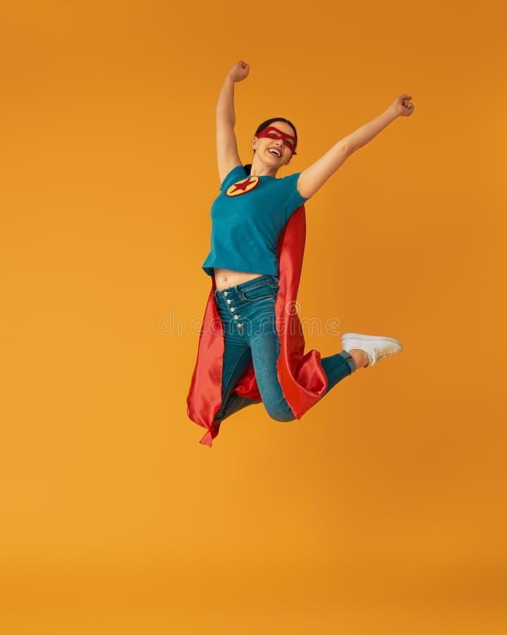 Woman in superhero costume. Joyful beautiful young woman in superhero costume posing on yellow background royalty free stock photo