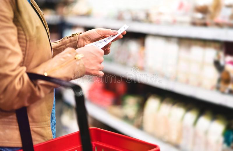 Woman in supermarket aisle with food shelf reading shopping list. And holding basket. Woman buying groceries in store. Retail, sale and consumerism concept stock photos