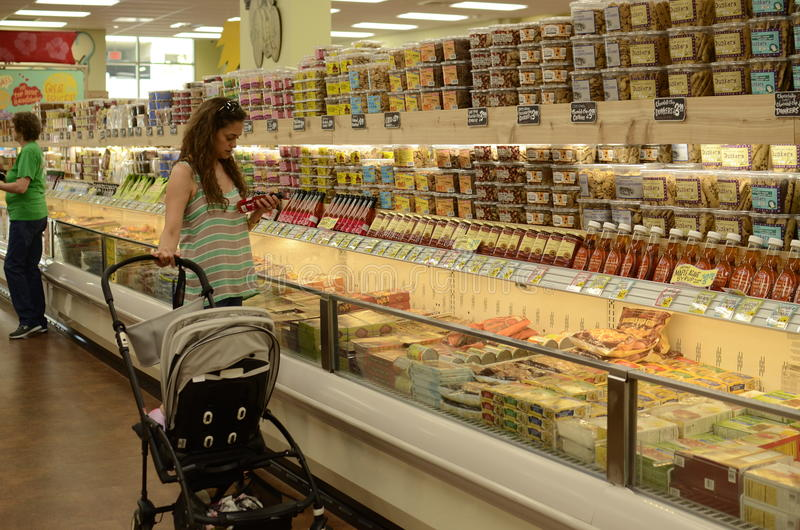 Woman in supermarket aisle. Trader Joe's supermarket in Austin Texas royalty free stock images