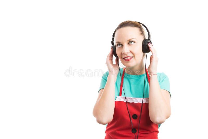 Woman supermarket employee listening music on headphones stock photos