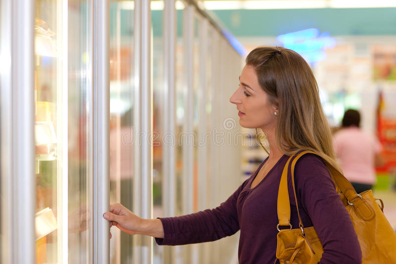 Woman in supermarket freezer section. Woman in a supermarket standing in front of the freezer looking for his favorite frozen food stock photo