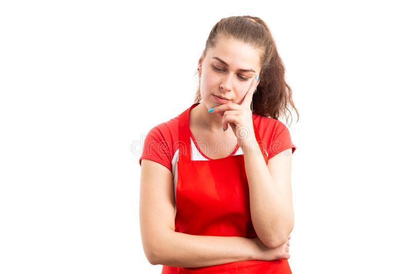 Woman supermarket or hypermarket employee thinking. Young woman supermarket or hypermarket employee thinking with serious expression as worried worker concept royalty free stock images