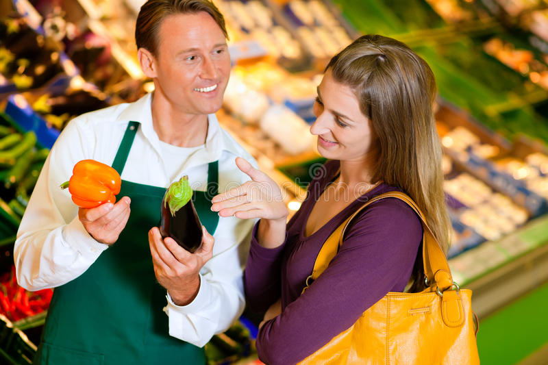 Woman in supermarket and shop assistant stock images