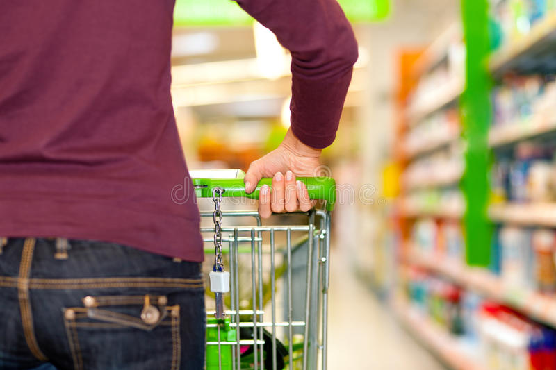 Woman in supermarket with shopping cart royalty free stock photos