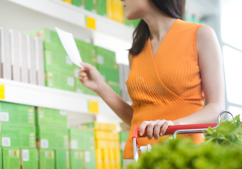 Woman at supermarket with shopping list stock image